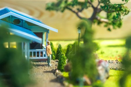Photo for Figurine of man is standing by the house. Living in the country. Eco-friendly housing. Construction of private houses. - Royalty Free Image