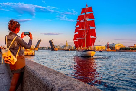 Photo for Saint Petersburg. Russia. Holiday Scarlet Sails. Sailboat sailing on the Neva River. The girl takes pictures on the phone. Holiday graduate school. Sailboat with scarlet sails in St. Petersburg. - Royalty Free Image