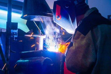 Photo pour Soudeur au travail. Un homme soude des pièces métalliques sur le lieu de travail. Matériel de soudage. Soudage à l'usine. Métallurgie. Étincelles de soudage. - image libre de droit