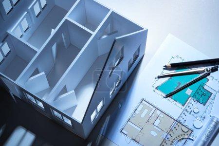 Photo pour Dessins près de la vue de dessus de la maison. Services d'élaboration de dessins. Créer un plan de la maison. Un petit exemplaire d'une maison sans toit. Le projet de rénovation du bâtiment. Aménagement du mobilier. - image libre de droit