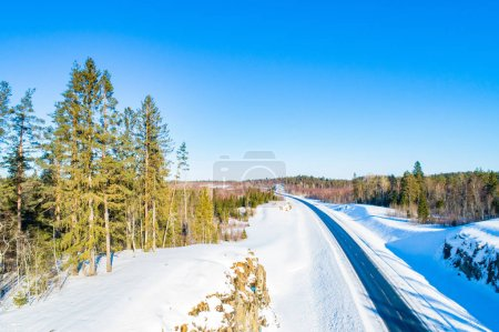 Photo pour Russia. Winter landscape. The road goes away. nature of Russia. Snow and pines on the roadside. A tourist trip in the winter. Rest in Karelia. Holidays away from the city - image libre de droit