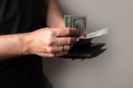 Photo for A man counts money. Wallet and dollars. The cost of the consumer basket. Income and expense analysis. The management of the budget of the family. Rise in prices. Inflation. - Royalty Free Image