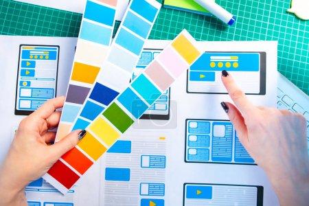 Photo pour Développement d'applications mobiles. Sélectionnez le schéma de couleurs pour le programme. Concepteur d'applications mobiles au travail. Développement d'un projet de conception de programmes supplémentaires pour les gadgets électroniques . - image libre de droit