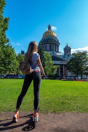Photo pour La Russie. Saint-Pétersbourg. Cathédrale Saint Isaac. La fille sur le scooter. Une fille en scooter à Pétersbourg. Un étudiant regarde la cathédrale Saint-Isaac. Tours à Saint-Pétersbourg. Voyager en Russie. - image libre de droit