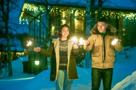 Photo for Girl and boy holding sparklers. Sparklers are on. A young couple celebrates Christmas. Young people in the background of the cottage with garlands. New year out of town. - Royalty Free Image