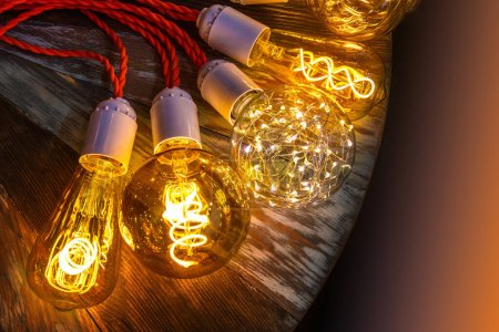 Photo for Glowing bulbs of unusual shapes on a wooden base. Lighting of premises. Design of restaurants and offices. The light from spirals. Modern lighting options. Lamps with red laces. - Royalty Free Image