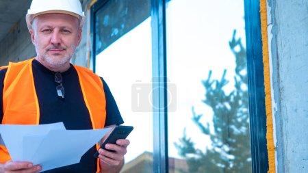 Photo pour Bâtisseur. Homme sur un chantier. Concept de travail en tant que constructeur. Homme adulte en uniforme de bâtiment. Architecte sur un chantier. Ouvrier constructeur. Un homme avec un casque de construction. Constructeur avec téléphone - image libre de droit