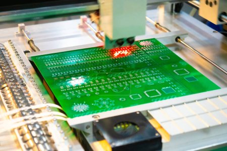 Photo for Production of printed circuit boards. The machine assembles the printed circuit Board in accordance with the program. Production automation. PCB Assembly without human intervention. Radionics. - Royalty Free Image