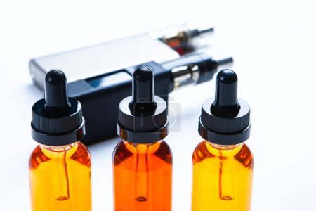 Photo for Liquids for Smoking on the background of vapes. Flavored liquids for Smoking. The bottles are filled with mixtures of different colors. Variety of vaping accessories. Smoking electronic cigarettes. - Royalty Free Image