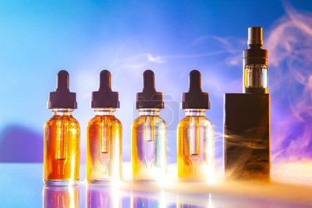 Photo for VAPE and vials of liquids are on the table. Accessories for vaping brightly lit. VAPE shop. The concept of vaping. Smoking vape. Electronic cigarette. - Royalty Free Image