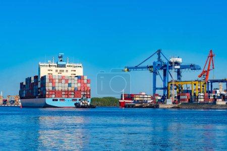 Photo pour Le navire marchand est chargé de conteneurs colorés. Le travail du port maritime commercial. Des grues dans le port effectuent des opérations de chargement et de déchargement. Paysage du port en bleu. Cargaison - image libre de droit