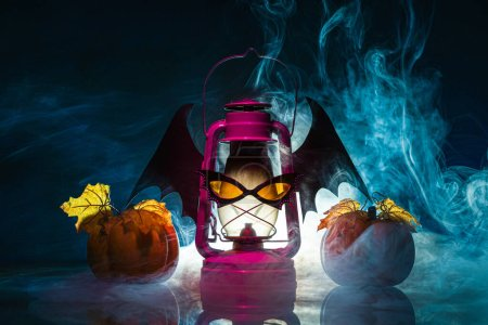 Photo for Halloween. Autumn holiday. Pumpkins and a lantern with bat wings on a black background. Still life in smoke. Prepare for the celebration of Halloween. - Royalty Free Image