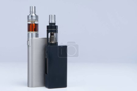 Photo for Two vapes on a white background. The concept of vaping. VAPE shop. Smoking electronic cigarettes. Sale of e-cigarettes. Place for inscription. Two models of electronic cigarettes. - Royalty Free Image