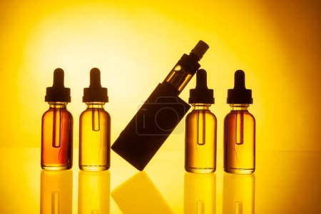 Photo for Electronic cigarette and liquid on yellow background. Selling VAPE. Vaping accessories. Gadgets for vaper. Smoking electronic cigarettes. Smoking liquid. Replacing conventional cigarettes. - Royalty Free Image