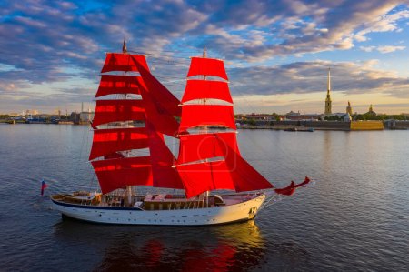 Photo for A ship with scarlet sails on the Neva. Sailboat in the center of Saint Petersburg. Sailboat on the background of the Peter and Paul fortress. Scarlet sails. A schooner with sails and a Russian flag. - Royalty Free Image