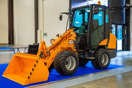 Photo for Backhoe loader. A small excavator is in the hangar. Loading equipment. Equipment for work in the warehouse. Yellow excavator in a building. Sale of street cleaning equipment. - Royalty Free Image