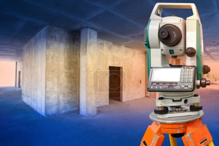 Photo for The surveyor works in a building under construction. Geodetic measurements. Construction equipment. Theodolite is installed in a house under construction. - Royalty Free Image