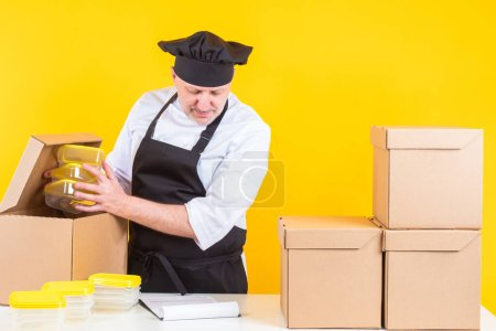 Photo for Chef checks incoming kitchen equipment. Chef holds plastic containers in his hands. Man unpacks boxes. Restaurant cook takes out plastic containers. Chef yellow background. Takeaway food containers - Royalty Free Image