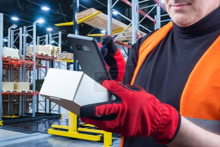 Photo for Man uses application for inventory control. Man in a warehouse holds phone in his hands. Storekeeper uses application on phone. Storekeeper photographs a small box. Application for warehouse business - Royalty Free Image