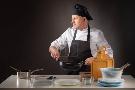 Photo for Chef cooking in kitchen. Male chef is cooking something. Chef in restaurant kitchen. Adult cook holds a skillet in his hands. Cook with a frying pan on a dark background. Cook in kitchen looks away - Royalty Free Image
