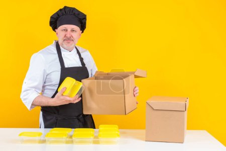 Photo for Chef cook man unpacks boxes. Cook takes out kitchen equipment. Plastic containers in hands of chef. Concept - sale inventory for restaurant. Chef takes out new dishes. Restaurant delivery containers - Royalty Free Image