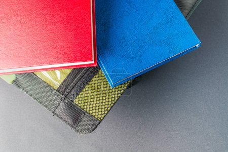 Red and blue book lies on a laptop bag....