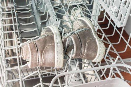 Photo pour Chaussures pour enfants se trouvent dans la machine à laver le lave-vaisselle . - image libre de droit