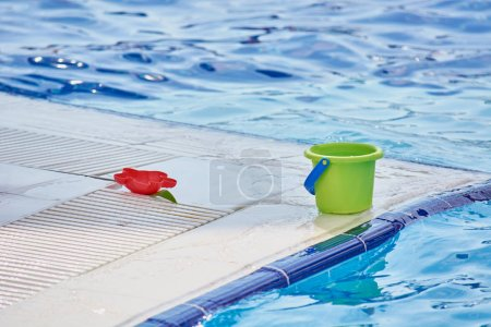Photo for Green bucket on edge of blue pool for playing children - Royalty Free Image