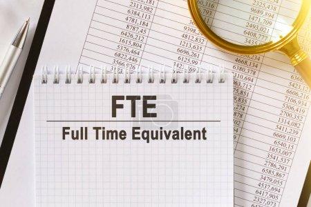 Photo pour Sur la table se trouvent des rapports financiers, un stylo, une loupe et un carnet avec l'inscription FTE. Équivalent temps plein. Concept d'entreprise et de finance. - image libre de droit