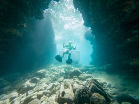 Male diver swimming through natural underwater tunnel.