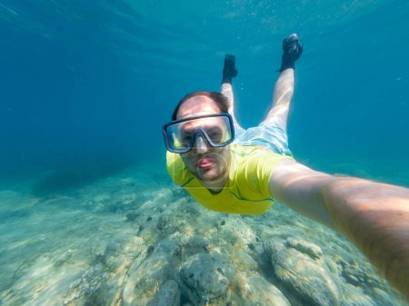 Male diver taking a selfie while snorkling.
