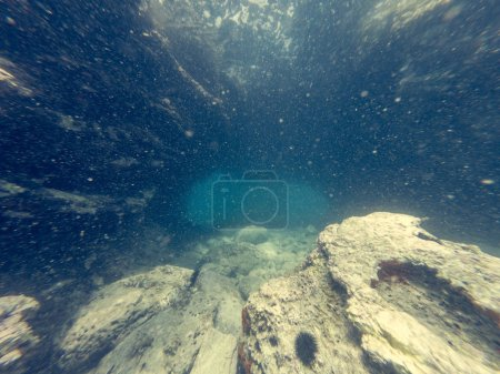 Diving through natural underwater tunnel at sea.