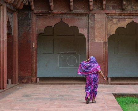 Photo pour Une femme en costume traditionnel (sari) à pied au Fort d'Agra à Agra (Inde) - image libre de droit