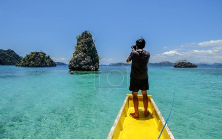 Photo for A young man standing on wooden boat and looking at the seascape of Coron Island, Philippines. - Royalty Free Image