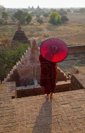 Photo for A young monk standing on top of ancient Buddhist temple in Bagan, Myanmar. - Royalty Free Image