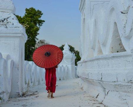 Photo pour Un moine bouddhiste novice avec un parapluie rouge marchant au temple blanc . - image libre de droit