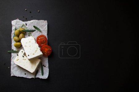 Foto de Queso griego Feta con tomates y aceitunas sobre fondo negro - Imagen libre de derechos