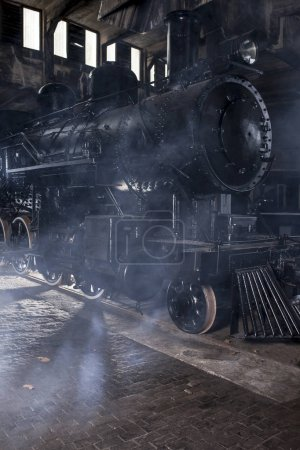 Locomotive à vapeur à la gare avec vapeur et éclairage spectaculaire