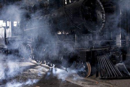 Locomotive à vapeur à la gare avec éclairage spectaculaire et vapeur