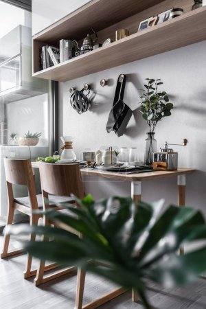 Photo for Stylish dining table corner with dishware and plants in Scandinavian style apartment - Royalty Free Image