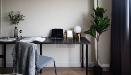 Photo for Bedroom working corner decorated with laptop, white candles and artificial plant in glass vase on black wood  working table with beige painted wall in the background /apartment interior / copy space - Royalty Free Image