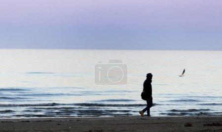 Photo pour Silhouette de l'homme restant en mer sur le coucher du soleil - image libre de droit