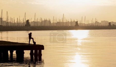 Photo for Man standing at pier, sunset view - Royalty Free Image