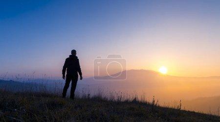 Photo pour Homme regardant le paysage étonnant de coucher du soleil - image libre de droit
