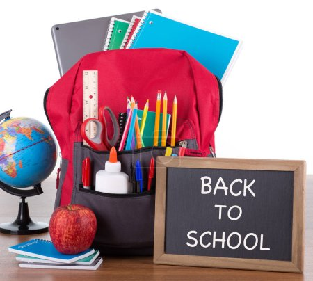 Photo for Backpack with an assortment of school supplies with BACK TO SCHOOL written on a chalkboard on a wooden desktop and white backkground - Royalty Free Image