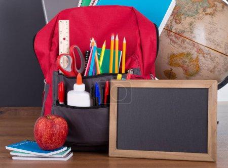 Photo pour Assortiment de fournitures scolaires dans un sac à livres avec un tableau blanc sur un bureau en bois - image libre de droit