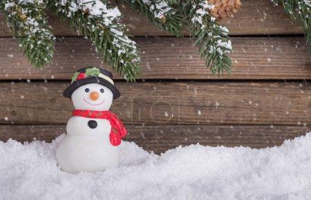 Photo pour Figurine de bonhomme de neige de vacances sur neige avec des banquettes persistantes sur un fond de bois avec chute de neige - image libre de droit