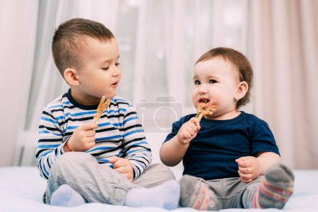 Photo for Brother and sister eat lollipops in the form of a cock - Royalty Free Image