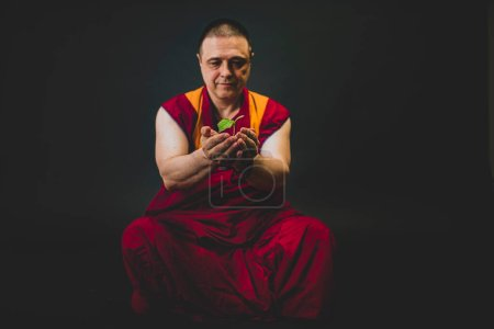 Photo for Buddhist monk in red kesa. A monk holding a green plant in his hand - Royalty Free Image