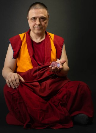 Photo for Buddhist monk in red kesa, holding a crystal of glass in his hand - Royalty Free Image